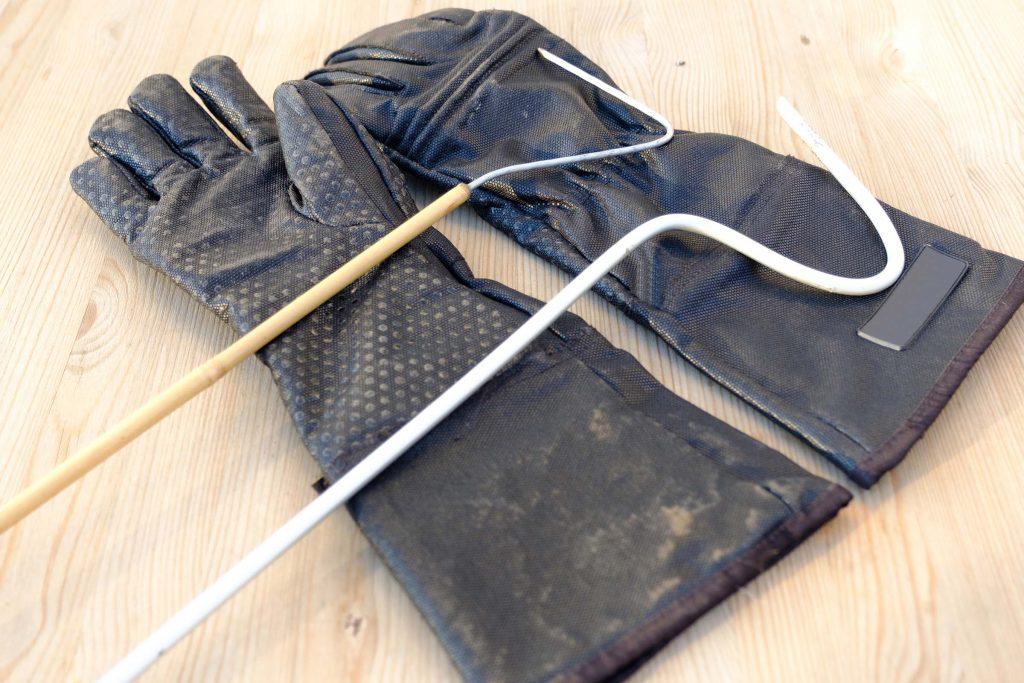 humane snake hook tool on top of gloves